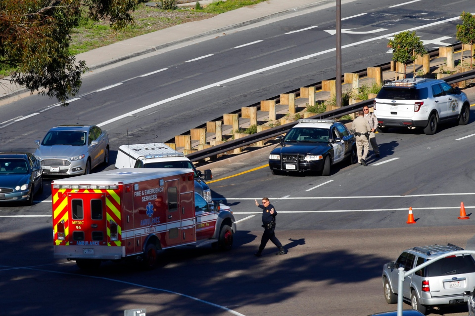 A law enforcement officer directs an emergency vehicle near the Naval Medical Center San Diego following a report of gunshots at a building on the campus of the complex, Tuesday, Jan. 26, 2016, in San Diego. (Nelvin C. Cepeda / The San Diego Union-Tribune)