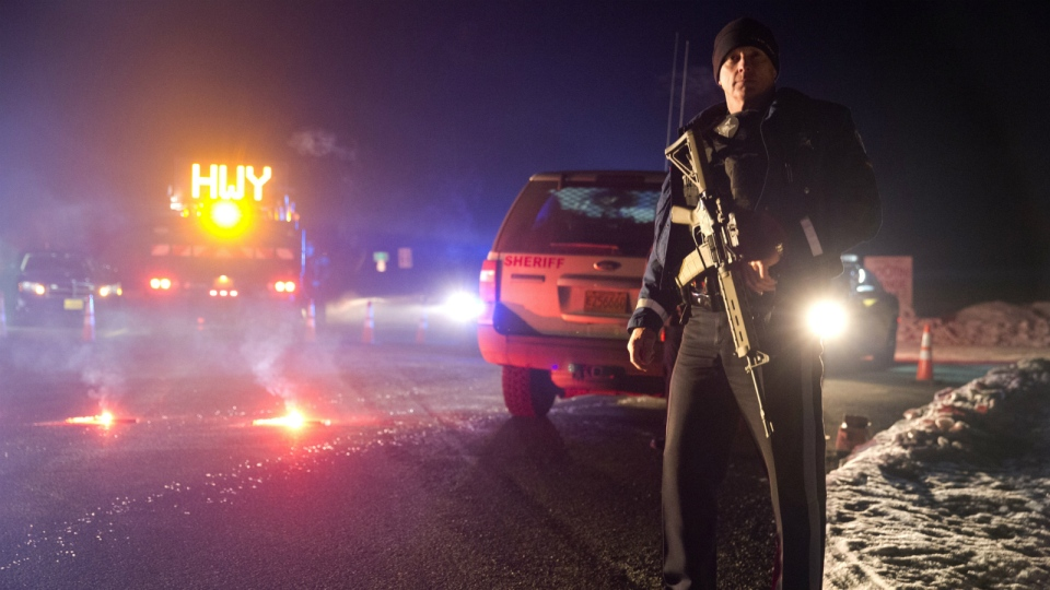 Sgt. Tom Hutchison stands in front of an Oregon State Police roadblock on Highway 395 between John Day and Burns by Oregon State police officers Tuesday, Jan. 26, 2016. (Dave Killen / The Oregonian)