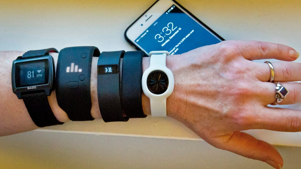 In this Dec. 15, 2014, file photo, fitness trackers, from left, Basis Peak, Adidas Fit Smart, Fitbit Charge, Sony SmartBand, and Jawbone Move, are posed for a photo next to an iPhone, in New York. (AP / Bebeto Matthews, File)