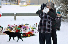 Residents console each other at the memorial near the La Loche Community School in La Loche, Sask., on Sunday, Jan. 24, 2016. (The Canadian Press/Jason Franson)
