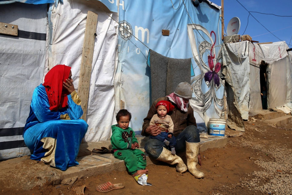 A Syrian family sit outside their tent, at a Syrian refugee camp, in the eastern town of Kab Elias, Lebanon on Jan. 27, 2016. (Bilal Hussein / AP Photo)