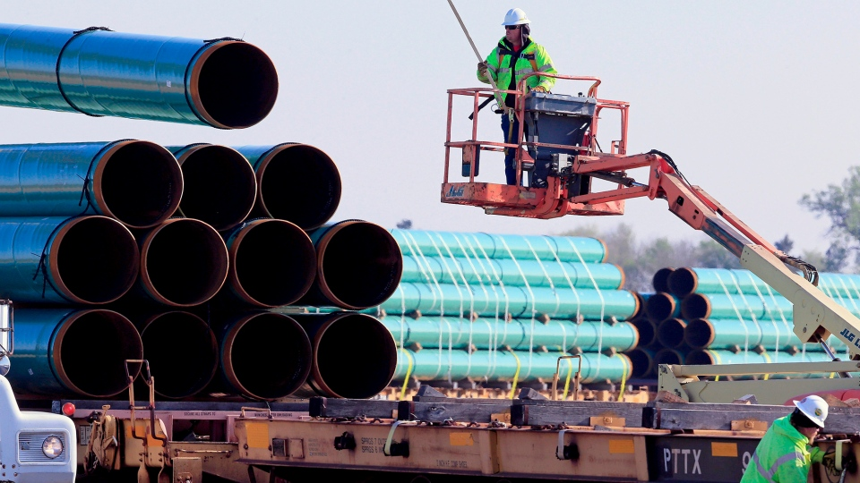 Workers unload pipes at a staging area May 9, 2015. (AP Photo / Nati Harnik)
