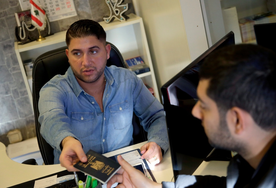 In this Jan. 26, 2016 photo travel agent Alaa Hadrous, left, hands over a passport to traveler Hussein Hotuman from Iraq, right, at the 'Golf Reisen' (Gulf Travels) travel agency in Berlin, Germany. (AP Photo/Michael Sohn)