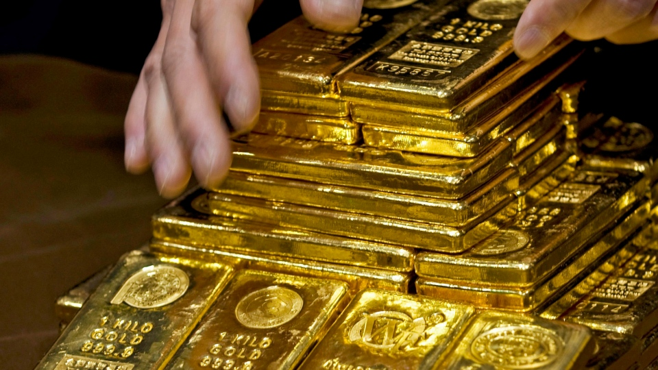 In an Oct. 17, 2011, file photo a staff member displays gold bullion bars during a news conference at the Chinese Gold and Silver Exchange Society in Hong Kong. (AP Photo)