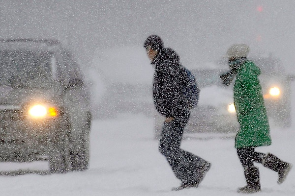 Pedestrians make their way across a snowy street in Montreal on Sunday, Dec., 21, 2008. (Graham Hughes / THE CANADIAN PRESS)