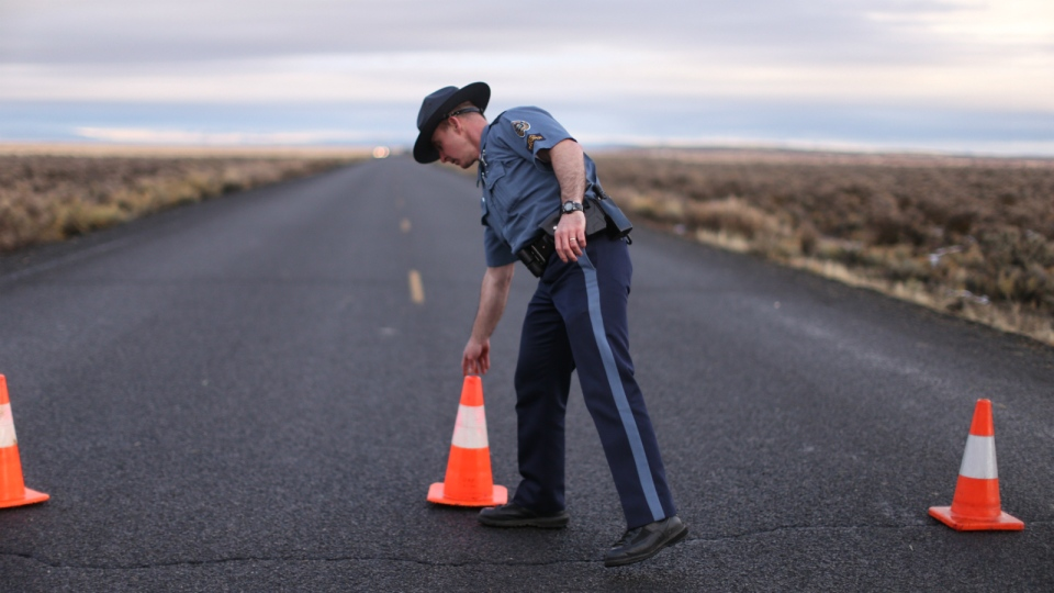 An officer with the Oregon State Police moves a cone to establish a roadblock along one of the routes to the Malheur National Wildlife Refuge in Harney County, Ore. on Jan. 28, 2016. (Beth Nakamura / The Oregonian)
