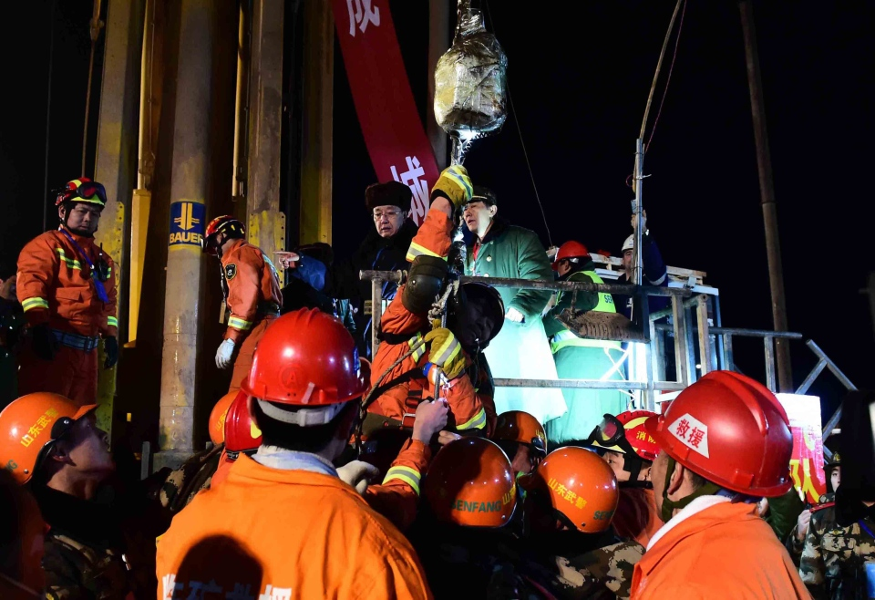 A miner, centre on hoist, is lifted from a collapsed mine in Pingyi, east China's Shandong Province, Friday evening Jan. 29, 2016. (Guo Xulei / Xinhua via AP)