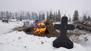 A fire burns as it thaws the frozen ground in order to dig a grave for one of the shooting victims at the cemetery in La Loche, Sask., Jan. 25, 2016. (Jonathan Hayward / THE CANADIAN PRESS)