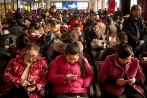 Passengers use their smartphones as they sit in a waiting room at the Beijing Railway Station in Beijing, Saturday, Jan. 30, 2016. (AP/Mark Schiefelbein)