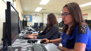 In this April 30, 2015 photo, Leticia Fonseca, 16, left, and her twin sister, Sylvia Fonseca, right, work in the computer lab at Cuyama Valley High School in New Cuyama, Calif. (AP / Christine Armario)