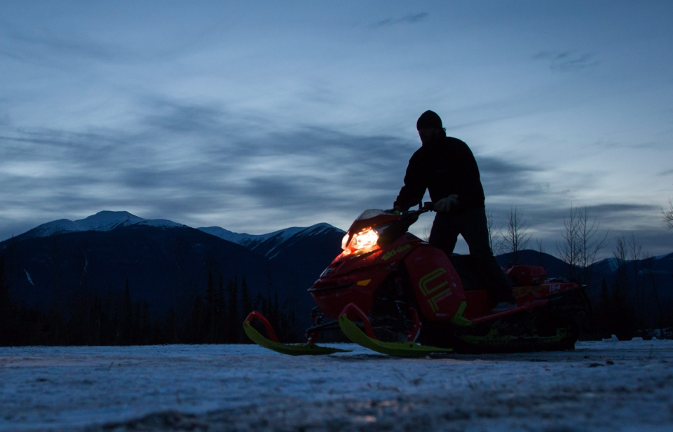Clint Pelletier, of Edmonton, Alta., is silhouetted while loading his snowmobile onto a trailer after snowmobiling with his wife at Mount Renshaw near McBride, B.C., on Saturday January 30, 2016.  (Darryl Dyck/THE CANADIAN PRESS)