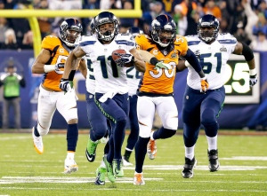 In this Feb. 2, 2014, file photo, Seattle Seahawks' Percy Harvin (11) runs from Denver Broncos' David Bruton (30) while returning a kickoff 87-yards for a touchdown during the second half of the NFL Super Bowl XLVIII football game, in East Rutherford, N.J. (AP/Ted S. Warren)