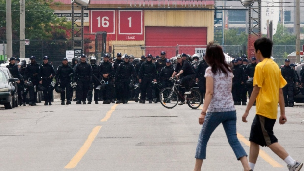 People walk across Pape Street as police officers in riot gear block the front of a temporary detention centre in Toronto, Sunday, June 27, 2010.(Jacques Boissinot /  THE CANADIAN PRESS)