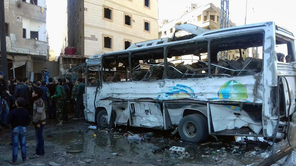 In this photo released by the Syrian official news agency SANA, Syrians gather where three bombs exploded in Sayyda Zeinab, a predominantly Shiite Muslim suburb of the Syrian capital, Syria, Sunday, Jan. 31, 2016. (SANA via AP)