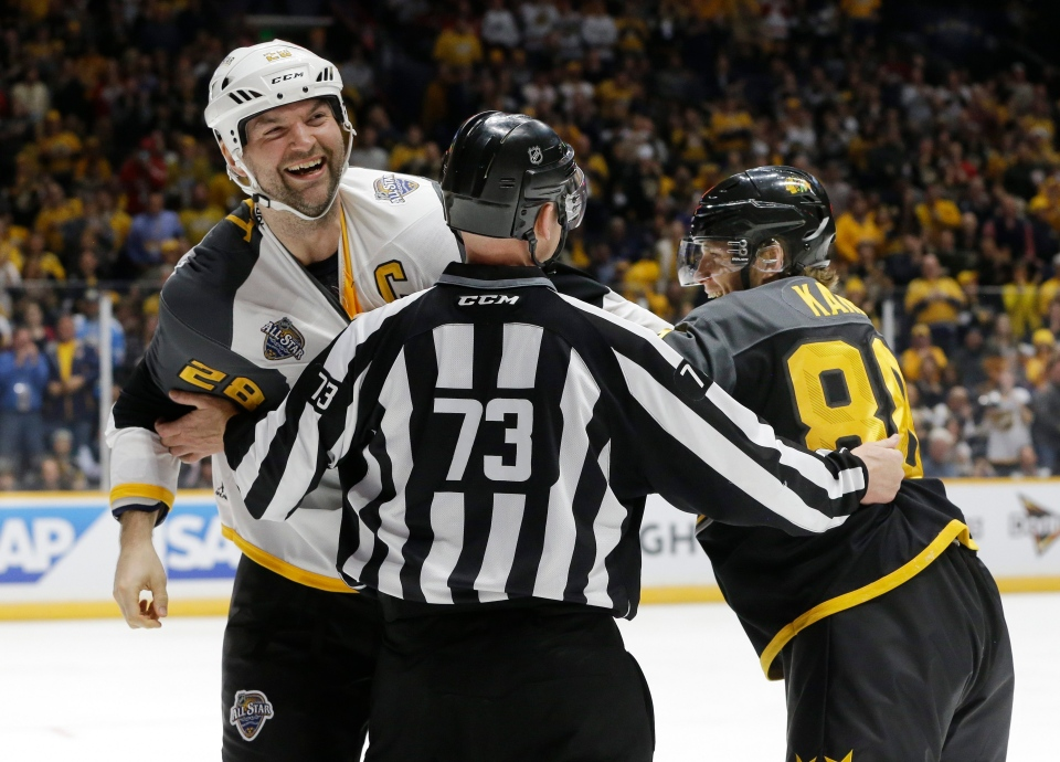 Pacific Division forward John Scott (28) and Central Division forward Patrick Kane (88), of the Chicago Blackhawks, pretend to fight after Scott knocked Kane to the ice during an NHL hockey All-Star semifinal round game on Jan. 31, 2016, in Nashville, Tenn. (Mark Humphrey / AP Photo)