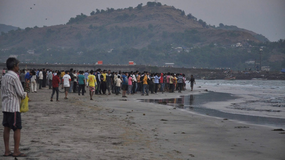 People gather on the beach after students were swept away at Murud on the Arabian Sea coast in Maharashtra state, India, on Feb. 1, 2016. (Sudhir Nazare / AP)