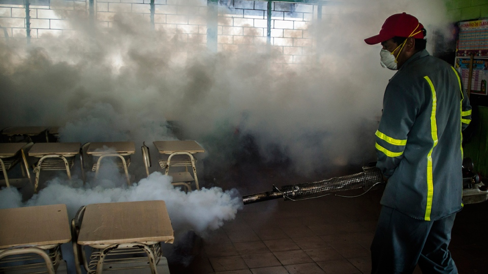 A city worker fumigates a classroom in a mosquito eradication effort to battle the insect blamed for spreading a virus suspected of causing birth defects, in Santa Tecla, El Salvador, Jan. 28, 2016. (AP / Salvador Melendez)