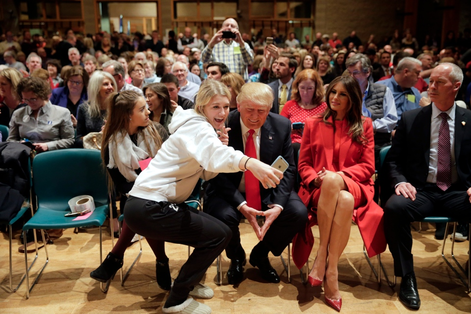 Republican presidential candidate Donald Trump, centre, accompanied with wife, Melania, second from right, pauses for a selfie while visiting Saint Francis of Assisi Church, a caucus site, Monday, Feb. 1, 2016, in West Des Moines , Iowa. (AP / Jae C. Hong)