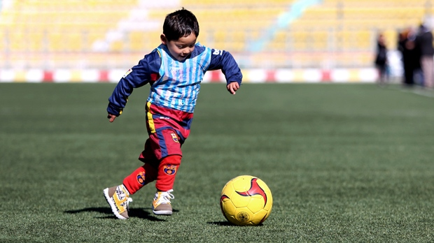 In this file photo, Martaza Ahmadi, a five-year-old Afghan Lionel Messi fan plays football, at the Afghan Football Federation Stadium in Kabul, Afghanistan, Tuesday, Feb. 2, 2016. (AP / Rahmat Gul)