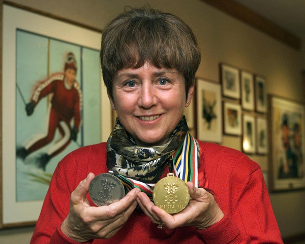 Nancy Greene holds up her gold and silver ski medals from the 1968 winter Olympics in Grenoble, France as she stands in front of pictures depicting her career Friday, Nov. 19, 1999 at Sun Peaks Resort near Kamloops, B.C. (Chuck Stoody / THE CANADIAN PRESS)