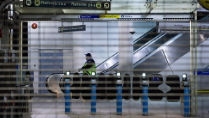 A worker is seen behind the locked gates of the Commercial-Broadway Skytrain station after the commuter train system was shut down to check for any possible damage to elevated guideways in Vancouver, B.C., in the early morning hours of Wednesday December 30, 2015, after an earthquake struck off the west coast late Tuesday night. (THE CANADIAN PRESS/Darryl Dyck)