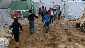 Syrian refugee children walk in mud from the heavy rain at a refugee camp in the town of Hosh Hareem, in the Bekaa valley, east Lebanon. (AP / Hassan Ammar)