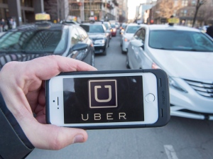 The Uber logo is seen in front of protesting taxi drivers who were depositing a request for an injunction against the ride sharing company at the courthouse in Montreal on Tuesday, Feb. 2, 2016. (Ryan Remiorz / THE CANADIAN PRESS)