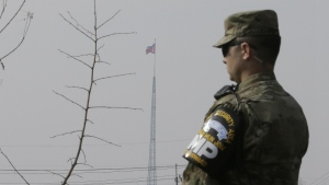 A North Korean flag flies in the propaganda village of Gijungdong as a U.S. Army soldier stands guard at Taesungdong freedom village near the border village of Panmunjom in Paju, South Korea, on Thursday, Feb. 4, 2016. (AP / Ahn Young-joon)