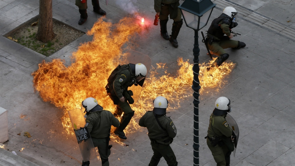 Riot policemen try to avoid a petrol bomb thrown by protesters during a 24-hour nationwide general strike in Athens on Thursday, Feb. 4, 2016. (AP / Thanassis Stavrakis)