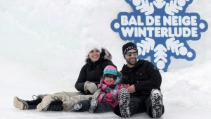 Karine Buteau (left), Olivier Vallee, and their daughter Khelya Vallee, 2, slide down an ice slide at Jacques-Cartier Park in Gatineau on the first weekend of the National Capital Commission's Winterlude Festival, on Sunday, Jan. 31, 2016. (Justin Tang / THE CANADIAN PRESS)