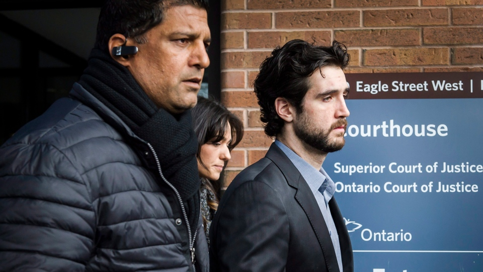 Marco Muzzo (right) leaves the Newmarket courthouse surrounded by family on Thursday, Feb. 4, 2016. (The Canadian Press/Christopher Katsarov)
