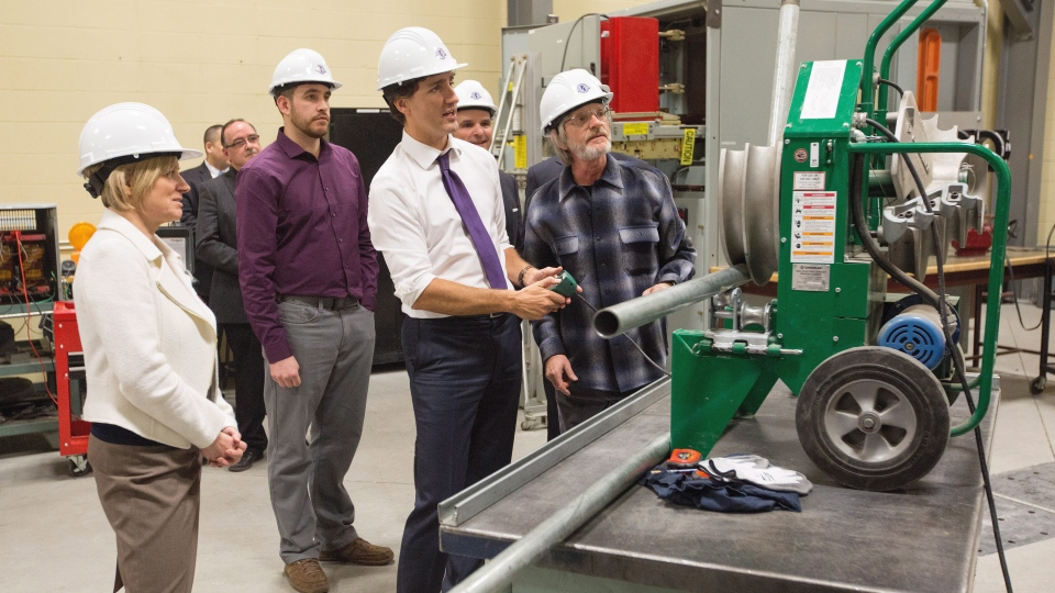Prime Minister Justin Trudeau bends a pipe during a tour of the International Brotherhood of Electrical Workers training facility as Alberta Premier Rachel Notley, left, looks on in Edmonton, Alberta, on Wednesday, Feb. 3, 2016. (THE CANADIAN PRESS/Amber Bracken)