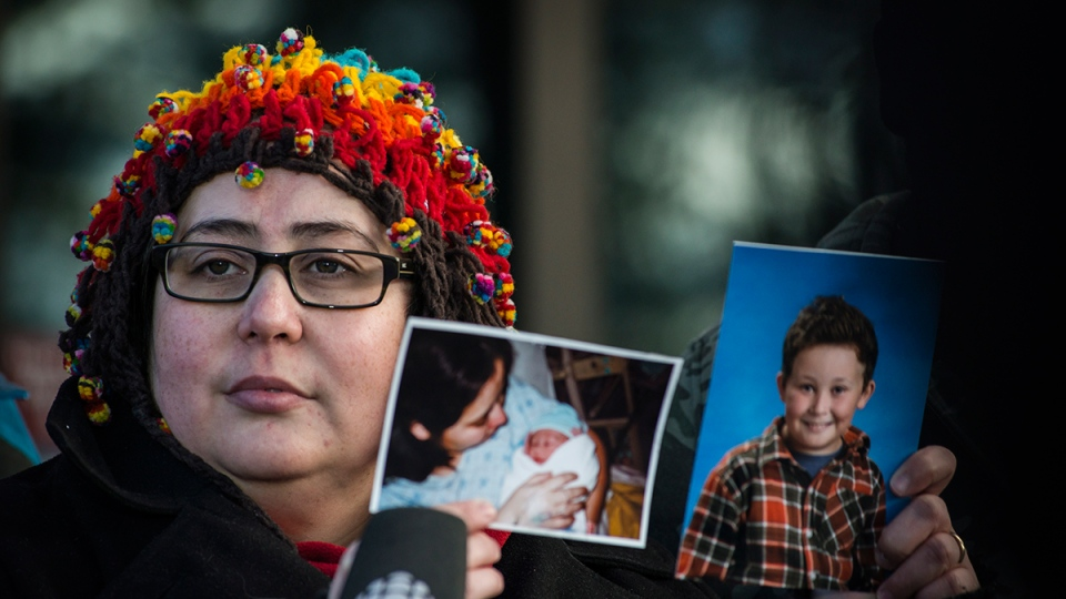 Jennifer Neville-Lake holds photos of her son Daniel as she gives a statement outside the Newmarket courthouse following the release of Marco Muzzo on bail on Thursday, Feb.  4, 2016. (Christopher Katsarov / THE CANADIAN PRESS)