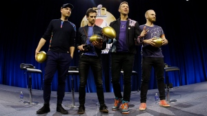 Jonny Buckland, left to right, Guy Berryman, Chris Martin and Will Champion of Coldplay hold footballs during a halftime news conference for the upcoming NFL Super Bowl 50 football game Thursday, Feb. 4, 2016, in San Francisco. (AP Photo / Matt Slocum)
