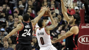 Portland Trail Blazers guard Damian Lillard drives to the basket on Toronto Raptors guard Norman Powell and forward Luis Scola during the first half of an NBA basketball game in Portland, Ore. on Thursday, Feb. 4, 2016. (AP / Steve Dykes)