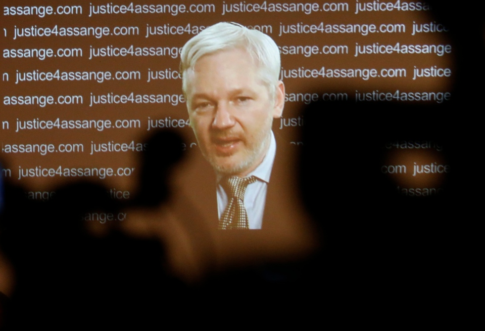 WikiLeaks founder Julian Assange is seen on a screen as he addresses journalists in foreground by video link from the London embassy of Ecuador, Friday Feb. 5, 2016. (AP/Frank Augstein)