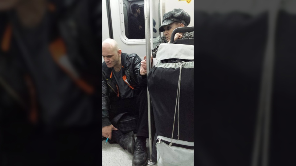 Ehab Taha recently captured this photo of an elderly woman holding the hand of a man who was sitting on the floor of Vancouver's Sky Train. (Ehab Taha / Facebook)