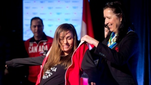 Tricia Smith, vice-president of the Canadian Olympic Committee presents Canadian snowboard team member Maelle Ricker of West Vancouver with her team jacket during the team announcement in Vancouver, Friday, Jan. 3, 2014. (THE CANADIAN PRESS / Jonathan Hayward)
