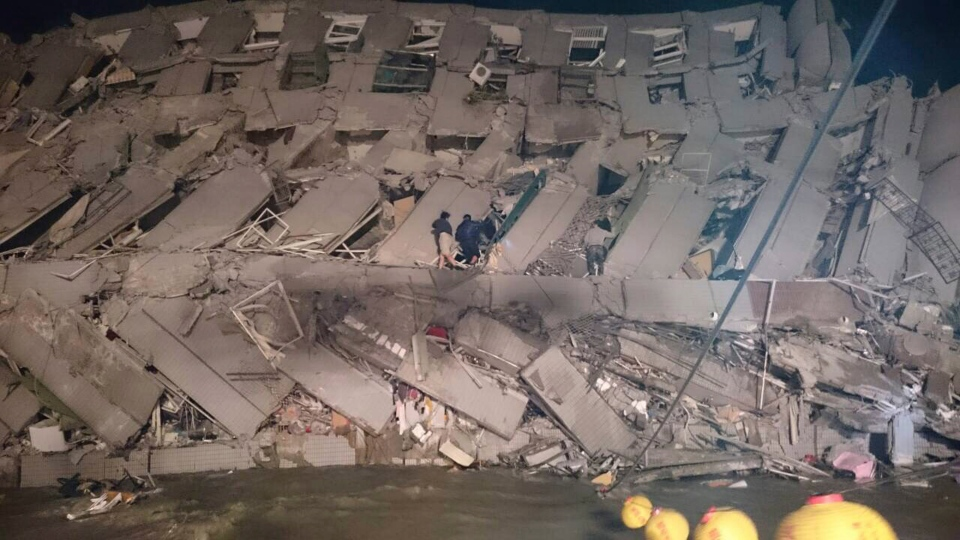 Rescuers are seen entering an office building that collapsed on its side from an early morning earthquake in Tainan, southern Taiwan, Saturday, Feb. 6, 2016. A 6.4-magnitude earthquake has struck southern Taiwan, according to the U.S. Geological Survey. (AP Photo)