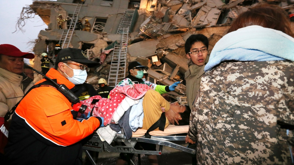 Rescue workers carry a man from the site of a toppled building after an earthquake in Tainan, Taiwan, Saturday, Feb. 6, 2016. (AP Photo)