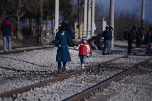 A woman with her child walk alongside railway tracks as refugees wait at a refugee camp to be allowed to continue their journey to Macedonia, near the northern Greek village of Idomeni, on Saturday, Feb. 6, 2016. (AP/Giannis Papanikos)