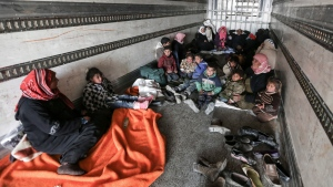 Syrians gather inside a truck to protect themselves from the cold weather at the Bab al-Salam border gate with Turkey, in Syria, Saturday, Feb. 6, 2016. (AP / Bunyamin Aygun)