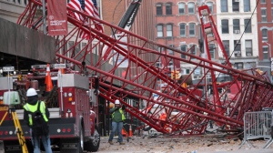 Firefighters and construction crews work on clearing a collapsed crane, Saturday, Feb. 6, 2016, in New York. Officials are working to determine why a huge construction crane that was being lowered during strong winds came crashing down onto a street. (AP Photo/Mary Altaffer)