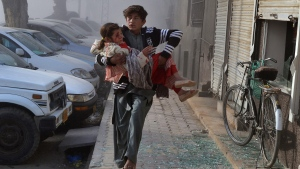 An injured boy carries an injured girl as he runs towards a safe area a few minutes after the suicide bombing in Quetta, Pakistan, Saturday, Feb. 6, 2016. (AP Photo / Arshad Butt)