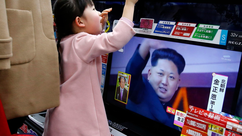 A girl watches a TV screen as all TV screens at an electronics store in Tokyo show a news program on North Korea's rocket launch with an image of North Korean leader Kim Jong Un, Sunday, Feb. 7, 2016. (AP / Shizuo Kambayashi)