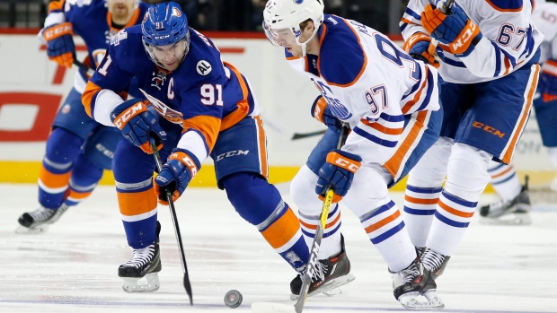 Edmonton Oilers center Connor McDavid (97) defends New York Islanders center John Tavares (91) in the first period of an NHL hockey game in New York, Sunday, Feb. 7, 2016. (AP Photo / Kathy Willens)