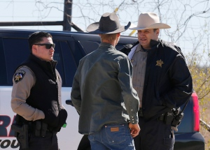 In this Saturday, Feb. 6, 2016 photo, Uvalde County Sheriffs Deputies talk with an individual while guarding the intersection to a neighbourhood several kilometres outside of Uvalde after a standoff resulted in multiple deaths. (Kin Man Hui, San Antonio Express-News via AP)