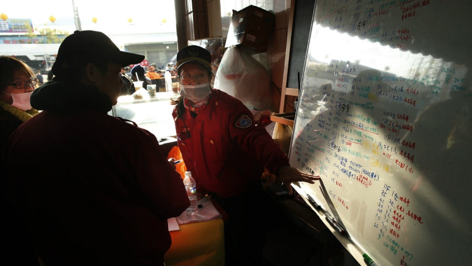 A rescuer points to a list of the survivors found in a collapsed building from an earthquake in Tainan, Taiwan on Sunday, Feb. 7, 2016. (AP / Wally Santana)