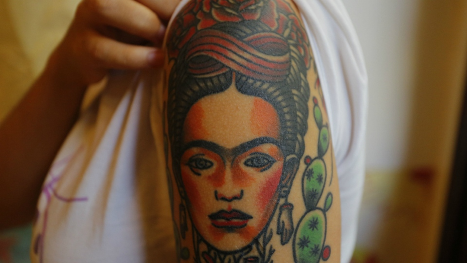Dione Lugones shows off her tattoo in the likeness of Mexican artist Frida Kahlo, at La Marca, or The Brand tattoo parlor in Havana, Cuba on Feb. 3, 2016. (AP / Desmond Boylan)