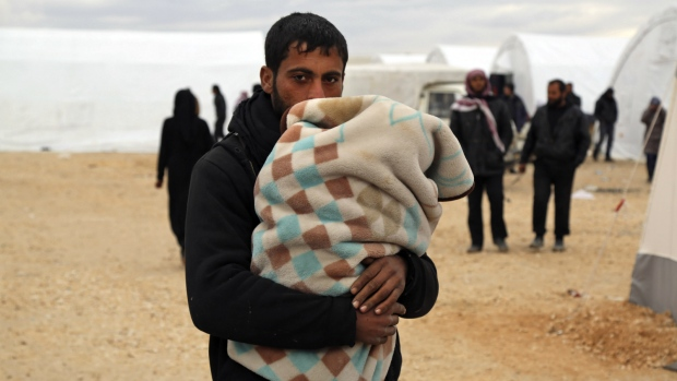 In this photo provided by Turkish Islamic aid group IHH, Syrians gather at a temporary refugee camp for displaced Syrians in northern Syria, near Bab al-Salameh border crossing with Turkey, Sunday, Feb. 7, 2016. (IHH)